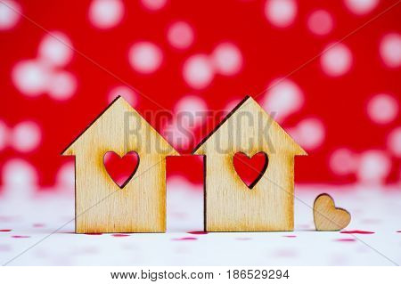 Two Wooden Houses With Hole In Form Of Heart With Little Heart On Red And White Background