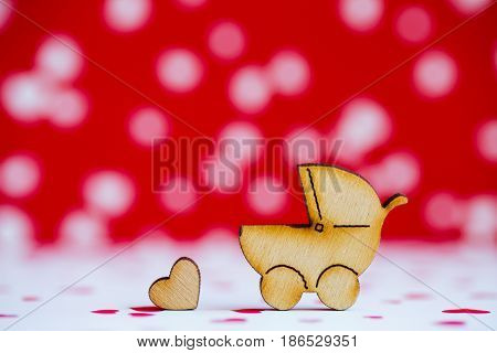 Wooden Icon Of Baby Buggy And Little Heart On Red And White Background