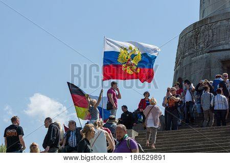 BERLIN - MAY 09 2016: Victory Day in Treptower Park. Guests and visitors at the foot of the monument to the Liberator Soldier with Russian and German flags.