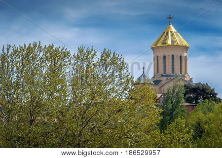 Architectural monuments of Tbilisi. The Sion Cathedral standing behind the green trees is shot on a sunny summer day.