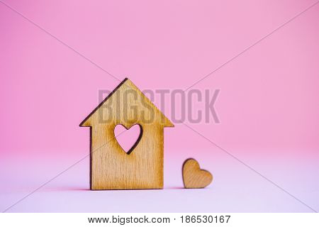 Wooden House With Hole In Form Of Heart With Little Heart On Pink Background