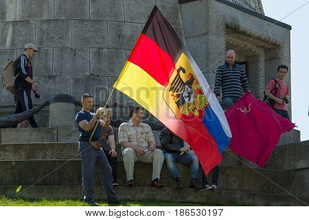 BERLIN - MAY 09 2016: Victory Day in Treptower Park. Guests and visitors at the foot of the monument to the Liberator Soldier with Russian German flag and the banner of Victory.