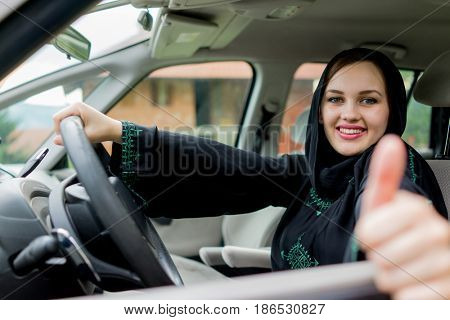happy muslim woman driving car