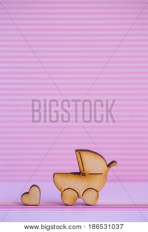 Wooden Icon Of Baby Buggy And Little Heart On Pink Striped Background