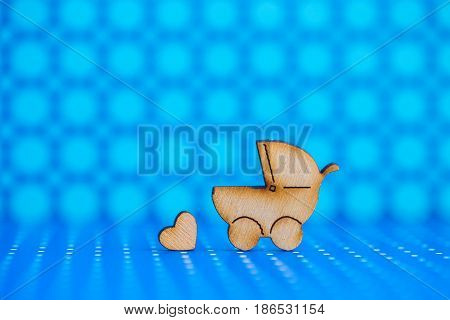 Wooden Icon Of Baby Buggy And Little Heart On Blue Spotted Background