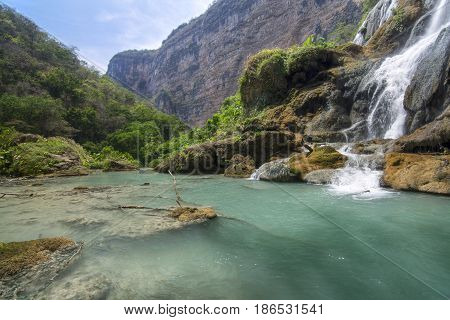 Beautiful turquoise blue pool under La Conchuda waterfall in scenic jungle landscape in rugged Rio la Venta Canyon in Chiapas Mexico on clear sunny day