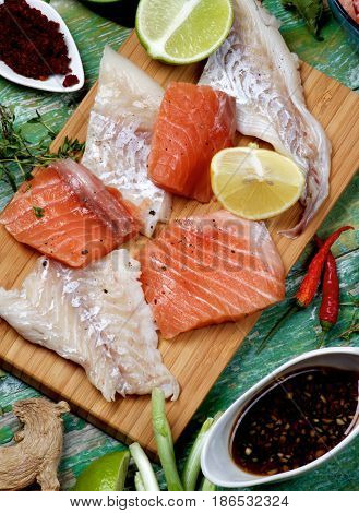 Arrangement of Raw Fillet of Salmon and Cod Greens Spices Sauces and Lemon closeup on Cracked Wooden background