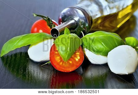 Caprese salad. Classic caprese salad. Italian traditional caprese salad ingredients. Mediterranean food. Caprese salad Tomato and mozzarella with basil leaves on wooden background.
