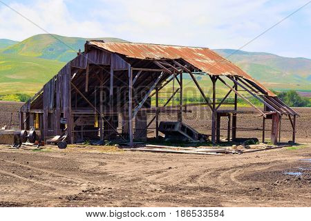 Abandoned collapsing wooden barn taken in the rural California Countryside