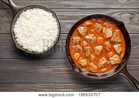 Goulash traditional Hungarian beef meat stew soup spicy gravy food in cast iron pan with rice on rustic vintage wooden table background