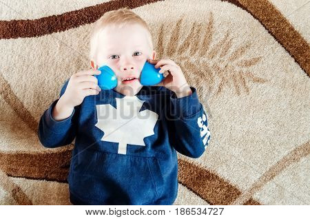 Boy Lies On The Floor And Shows Funny Eyes With Toys.