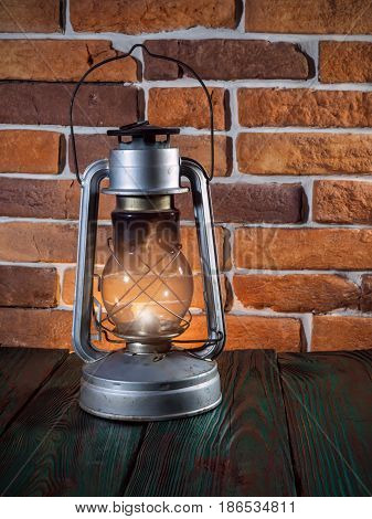Still life kerosene lamp shines on  wooden desktop  stone brick background