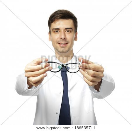 Handsome young ophthalmologist holding glasses on white background