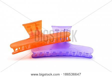 two hair claw clips of different colors, one orange and one violet, on a white background