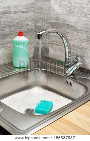 Kitchen Sink With Foam, Tap, Green Sponge And Detergent