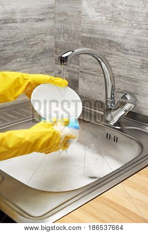 Hands In Yellow Gloves Washing Bowl Against Kitchen Sink