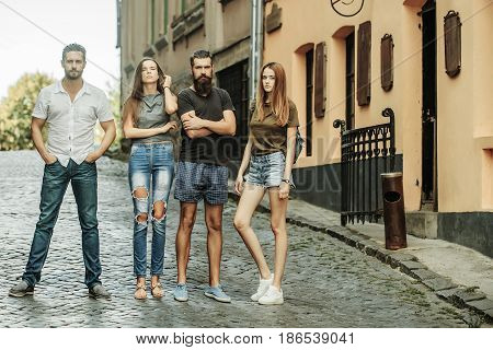 Young stylish fashionable friends or people pretty girls or cute women with long hair and unshaven handsome men or hipsters standing on brick road on city street. Friendship leisure summer