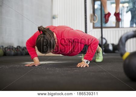Full length of fit female athlete doing pushups in health club