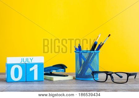 July 1st. Image of july 1 wooden color calendar on office suplies background. Summer day. Empty space for text.