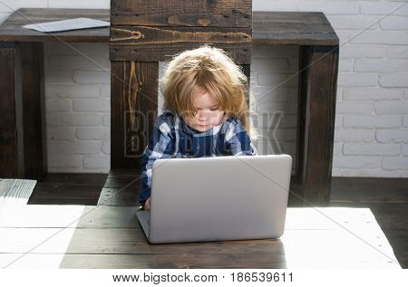 boss. small child boy with blonde hair work at laptop or computer with paper sheet on wooden table