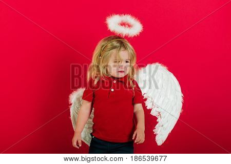 cupid. adorable little angel boy with white feather wings and halo crying kid with sad face and blonde hair on red background cupid on valentines day holiday