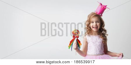 Small princess girl in crown holds a large spiral decorated lollipop candy