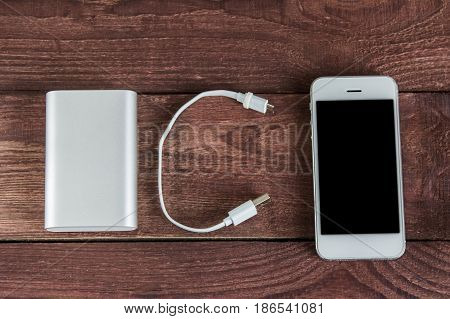 Portable External Battery ( Powerbank ) With Usb Cable And Smartphone On Wooden Table