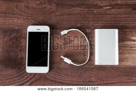 Portable External Battery ( Power Bank ) With Usb Cable And Smartphone On Wooden Background