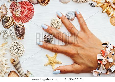 Young womans hand with shells and starfish on the white wooden table