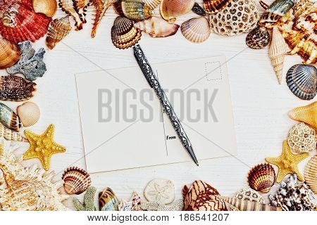 Postcard and a pen on the wooden table surrounded with sea shells in mediterranean style - horizontal top view