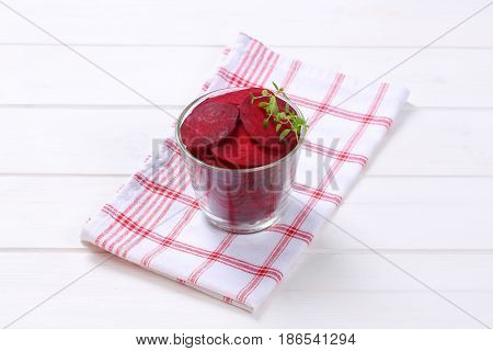 glass of thin beetroot slices on checkered dishtowel