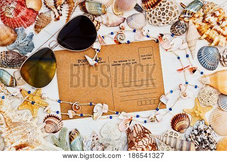 Vintage style blank postcard sunglasses and necklace with a frame of sea shells - top view in mediterranean style