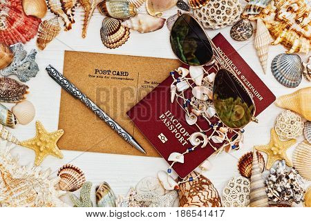 Russian passport vintage post card sunglasses and necklace made of sea shells on the table with frame of dozens sea shells in horizontal top view
