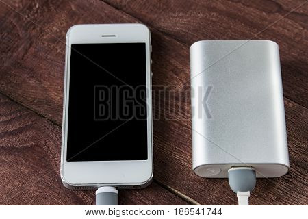 Grey Phone And Power Bank Connected By Cord