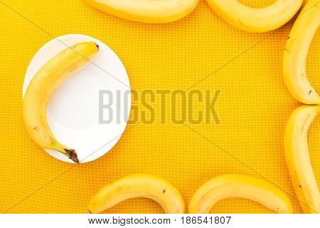 Several Yellow Ripe Bananas From The Tropics On A Yellow Fabric Background And A Banana On A White P