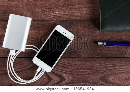 Grey phone and power bank connected by cord with pen and notebook .