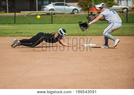 White uniform softball infielder waiting to tag diving black uniform runner.