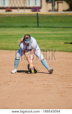 White uniform softball infielder picking up the ground ball in her glove.
