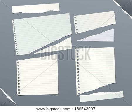 Pieces of ripped ruled, squared note, notebook, copybook paper sheets stuck on gray background