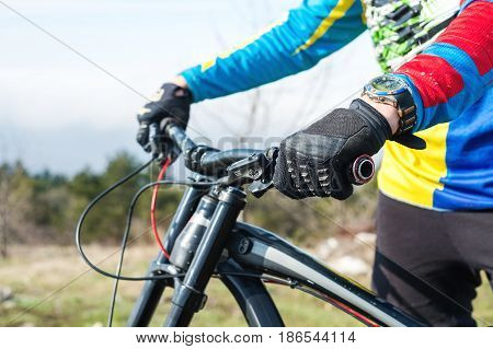 Hand Man racer mtb cyclist in sport gloves getting ready for a race firmly holds the steering wheel