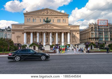 Moscow, Russia - 16 August 2016: Bolshoi Theater, Ohotniy Ryad street. The most famous theatre of Russia. Thousands of tourists annually visit the theatre in Moscow. Luxe car in front of the theater.