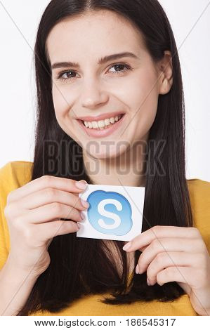 KIEV, UKRAINE - AUGUST 22, 2016: Woman hands holding Skype logotype icone printed paper close up. Is a telecommunications application software developed by Microsoft.