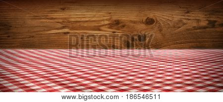 Tablecloth red checkered in front of a rustic wooden wall for a bavarian background