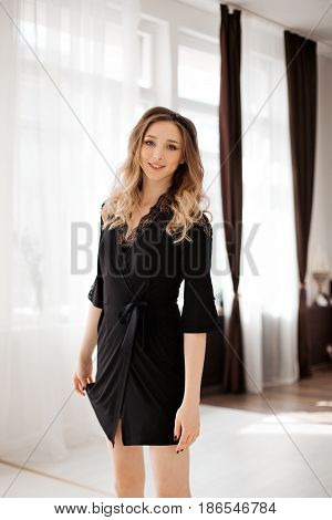 Portrait of beautiful smiling blonde girl wearing in black nightie dress  with wavy hair, and make up, posing at luxury interior of bedroom. Sexy morning look of gorgeous woman with perfect figure.
