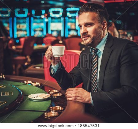 Upper class man behind gambling table in a casino