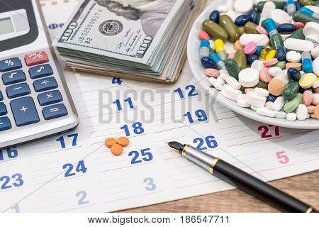 pills and dollar pen calculator on calendar.