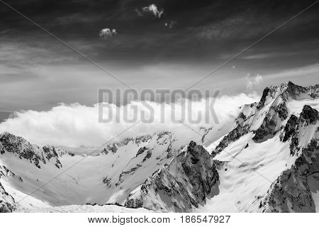 Black And White View On Snow Sunlight Mountains In Clouds