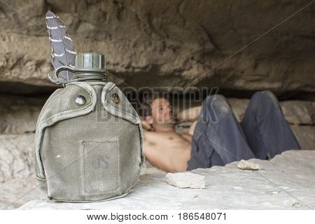 U.S. green military issue water canteen in foreground while army man reclines to rest on rocky ground in cave
