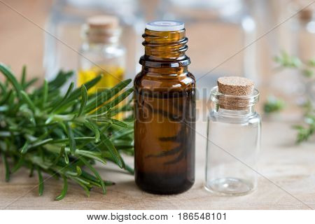 A Bottle Of Rosemary Essential Oil With Fresh Rosemary Twigs