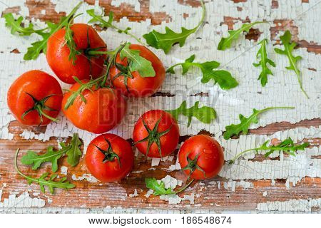 Fresh organic ripe tomatoes, basil leaves on wooden old shabby vintage table. Top view with copy space. Healthy eating concept, antioxidant and diet